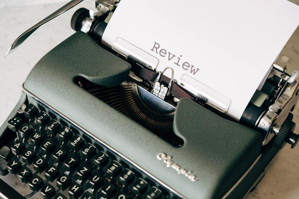 A photo of a typewriter with a page that has 'Review' typed onto it.